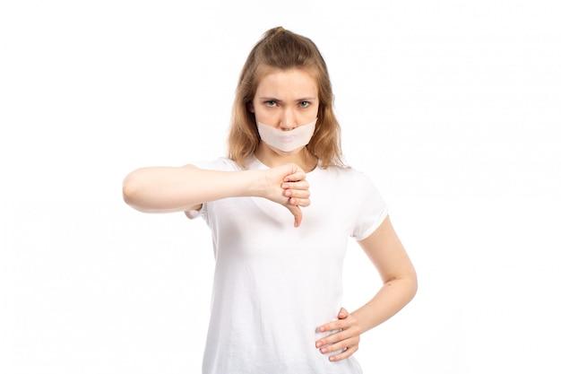 Widok z przodu młoda kobieta w białej koszulce z białym bandażem wokół ust, pokazująca inny znak na białym tle