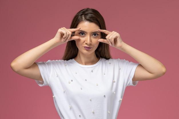 Widok z przodu młoda kobieta w białej koszuli pokazując oczy palcami na jasnoróżowej ścianie, pozie modelki