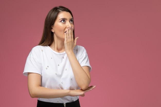 Widok z przodu młoda kobieta w białej koszuli pozuje z zaskoczonym wyrazem na różowej ścianie, zdjęcie kolorowej kobiety stanowią modelkę