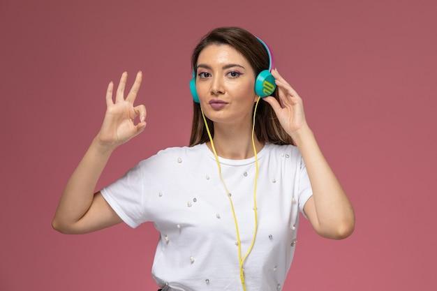 Widok z przodu młoda kobieta w białej koszuli, słuchanie muzyki i pozowanie na różowej ścianie, kolor kobiety stanowią model