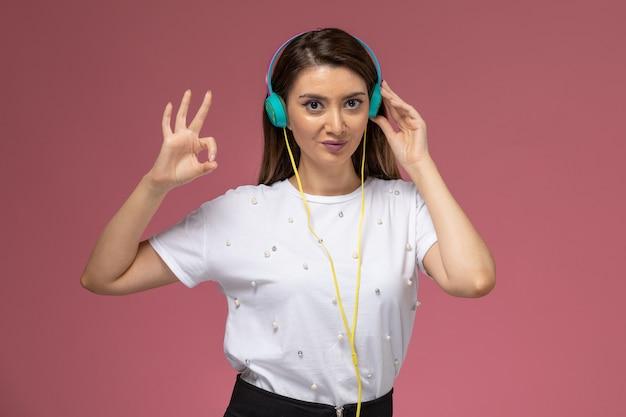 Widok z przodu młoda kobieta w białej koszuli, słuchanie muzyki i pozowanie na różowej ścianie, kolor modelki