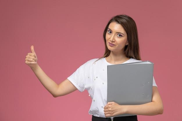 Widok z przodu młoda kobieta w białej koszuli trzymająca szary plik na różowej ścianie, modelka stanowi kobietę