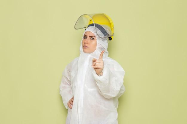 Widok z przodu młoda kobieta w białym specjalnym garniturze i żółtym hełmie ochronnym grożącym palcem na zielonym kombinezonie naukowym