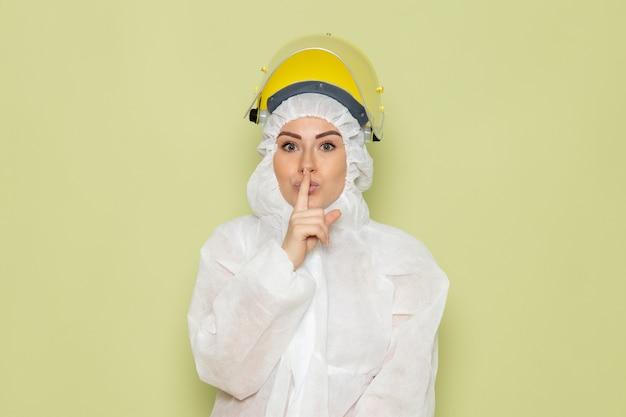 Widok z przodu młoda kobieta w białym specjalnym garniturze i żółtym hełmie ochronnym pokazująca znak ciszy na zielonym kombinezonie naukowym