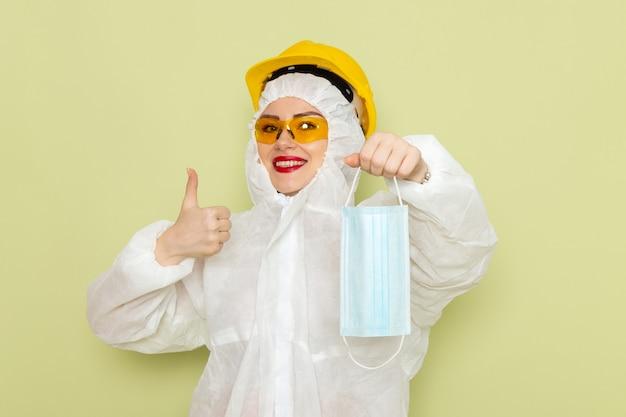 Widok z przodu młoda kobieta w białym specjalnym garniturze i żółtym hełmie trzymająca sterylną maskę z lekkim uśmiechem na zielonych pracach chemii przestrzeni