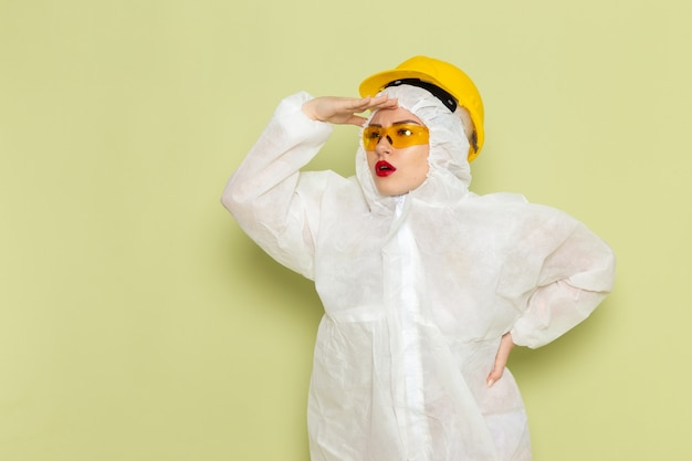 Widok z przodu młoda kobieta w białym specjalnym garniturze i żółtym kasku patrząc w dal na zielonej pracy