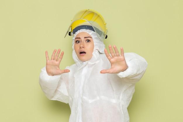 Widok z przodu młoda kobieta w białym specjalnym garniturze i żółtym kasku, pozowanie na zielonej pracy