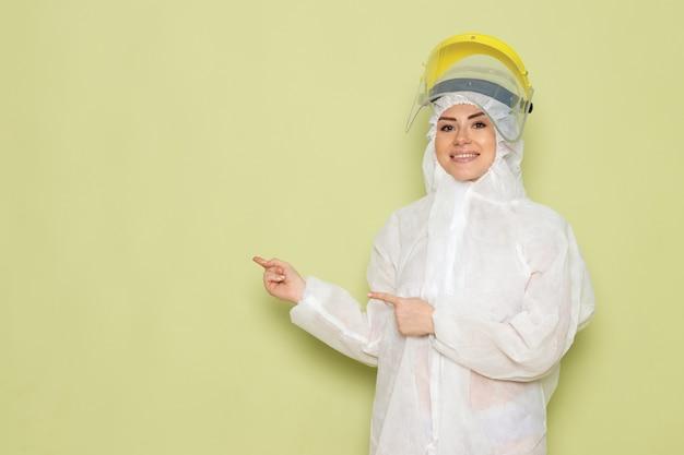 Widok z przodu młoda kobieta w białym specjalnym garniturze i żółtym kasku pozuje z uśmiechem na zielonym kombinezonie kosmicznym jednolitej pracy naukowej