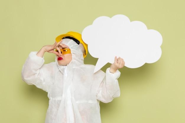 Widok z przodu młoda kobieta w białym specjalnym garniturze i żółtym kasku, trzymając biały znak zakrywający nos na zielonej przestrzeni chemii pracy s