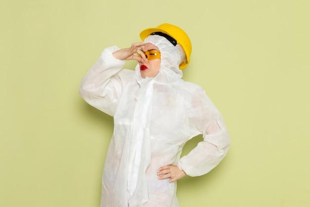 Widok z przodu młoda kobieta w białym specjalnym garniturze i żółtym kasku, trzymając nos na zielonej przestrzeni