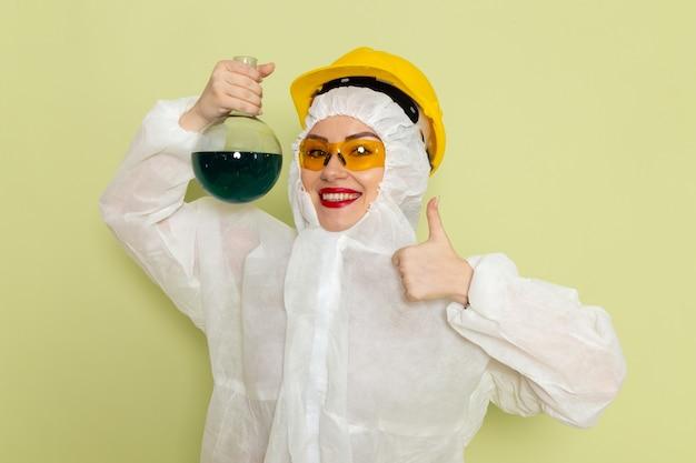 Widok z przodu młoda kobieta w białym specjalnym garniturze i żółtym kasku trzymając roztwór z uśmiechem na zielonej przestrzeni chemii pracy s