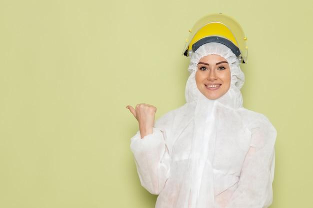 Widok z przodu młoda kobieta w białym specjalnym garniturze i żółtym kasku uśmiechnięta i pozująca na zielonym kombinezonie kosmicznym nauki
