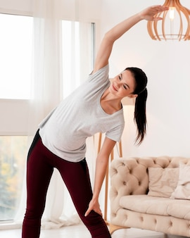 Widok z przodu młoda kobieta w ciąży ćwiczeń na macie fitness