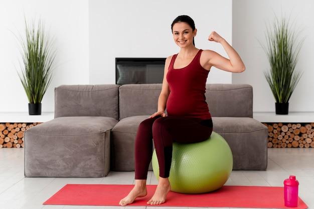 Widok z przodu młoda kobieta w ciąży za pomocą piłki fitness