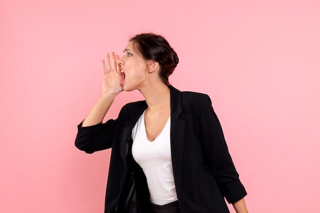 Widok z przodu młoda kobieta w ciemnej kurtce dzwoniąc do kogoś na różowym tle