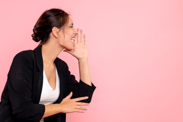 Widok z przodu młoda kobieta w ciemnej kurtce dzwoniąc na różowym tle