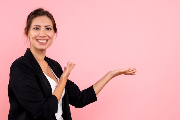 Widok z przodu młoda kobieta w ciemnej kurtce na różowym tle
