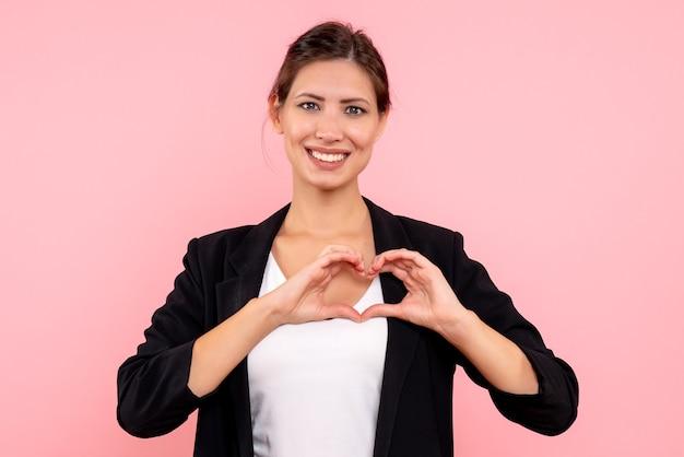 Widok z przodu młoda kobieta w ciemnej kurtce, uśmiechając się i wysyłając miłość na różowym tle