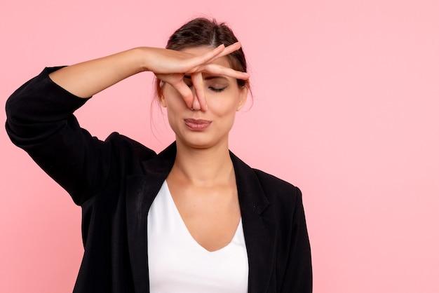 Widok z przodu młoda kobieta w ciemnej kurtce, zamykająca nos z powodu nieprzyjemnego zapachu na różowym tle