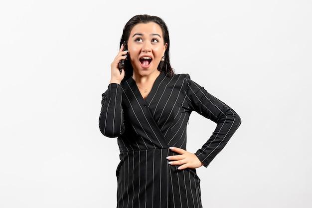Widok z przodu młoda kobieta w ciemnym surowym garniturze rozmawia przez telefon na białym tle kobieta dama moda pracownik praca piękno