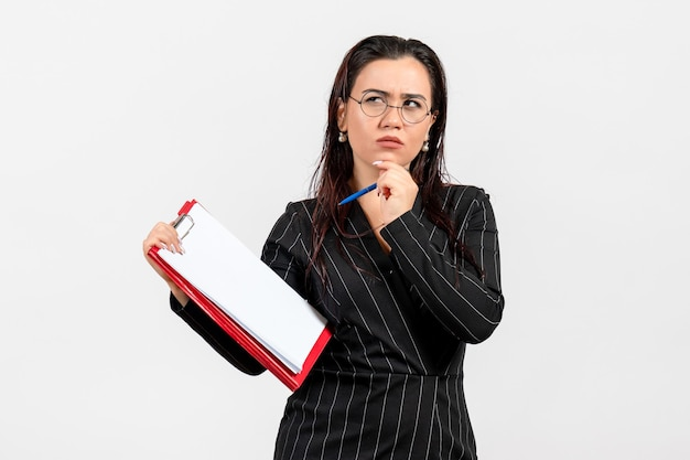 Widok z przodu młoda kobieta w ciemnym surowym garniturze trzymająca dokument i długopis na białym tle biznes kobiece dokumenty biurowe praca