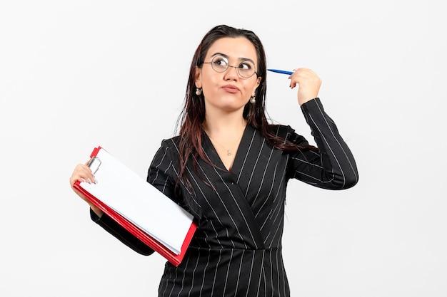 Widok z przodu młoda kobieta w ciemnym surowym garniturze trzymająca dokument i długopis na białym tle dokument biznes kobieta praca biurowa