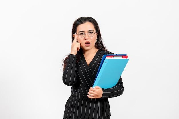 Widok Z Przodu Młoda Kobieta W Ciemnym Surowym Garniturze Trzymająca Dokumenty Na Białym Biurku Dokument żeński Praca Biurowa Darmowe Zdjęcia