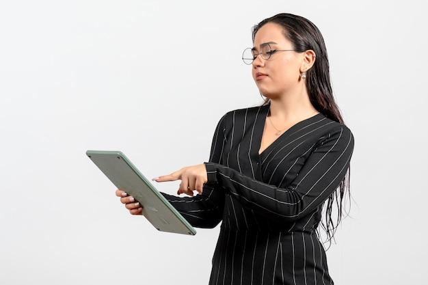 Widok z przodu młoda kobieta w ciemnym surowym garniturze trzymająca duży kalkulator na białym tle praca kobieta dama moda pracownik uroda