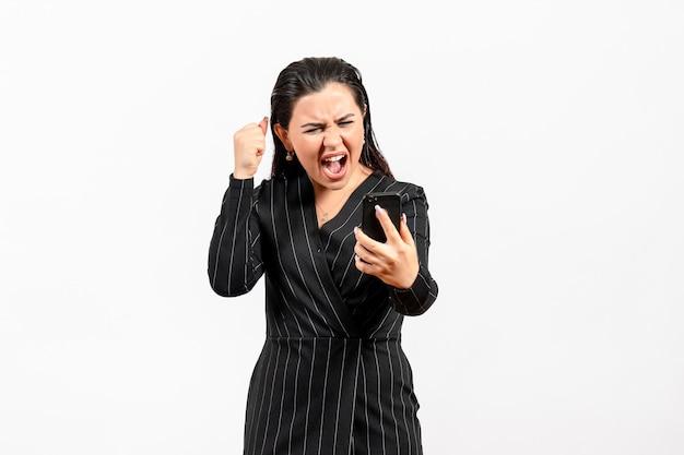 Widok z przodu młoda kobieta w ciemnym surowym garniturze trzymająca telefon krzyczy na białym tle kobieta dama moda pracownik biurowy praca uroda