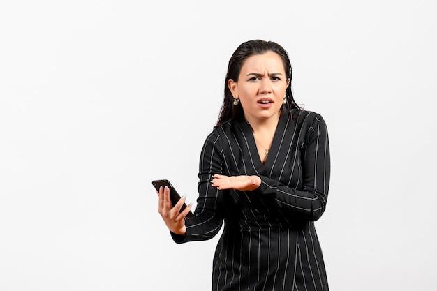 Widok z przodu młoda kobieta w ciemnym surowym garniturze trzymająca telefon na białym tle kobieta dama moda pracownik biurowy praca uroda