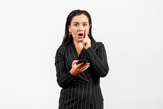 Widok z przodu młoda kobieta w ciemnym surowym garniturze trzymająca telefon na białym tle praca kobieta dama pracownik mody uroda