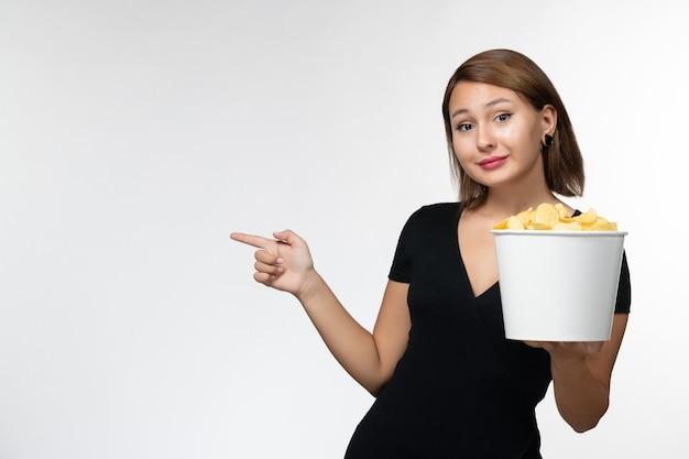 Widok z przodu młoda kobieta w czarnej koszuli trzyma chipsy na białej powierzchni