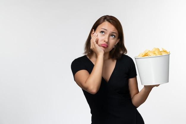 Widok z przodu młoda kobieta w czarnej koszuli trzyma chipsy ziemniaczane i myśli na białej powierzchni