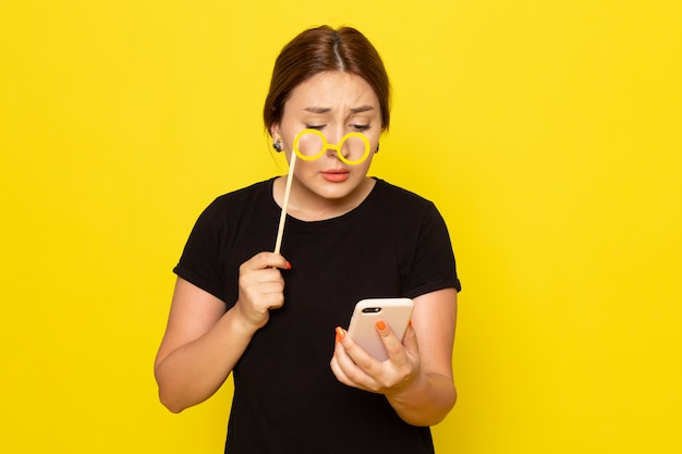 Widok z przodu młoda kobieta w czarnej sukience pozuje ze smartfonem i zabawkowymi okularami przeciwsłonecznymi na żółto