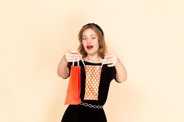 Widok z przodu młoda kobieta w czarnej sukience z łańcuszkami pasami trzymającymi pakiety na beżowym tle
