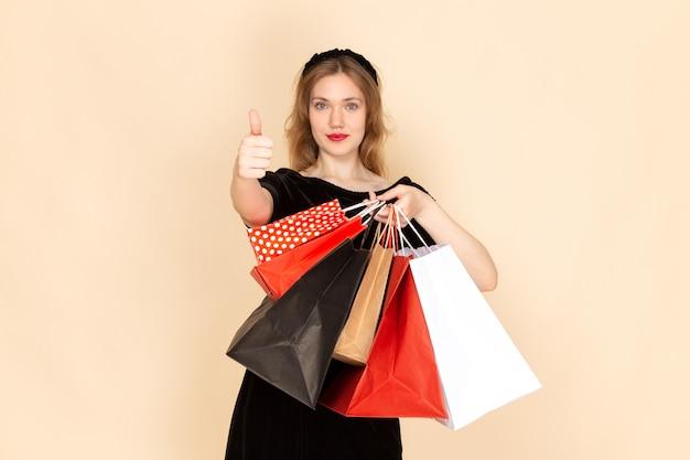 Widok z przodu młoda kobieta w czarnej sukni z paskiem łańcuchowym, trzymając pakiety zakupów na beżowym tle