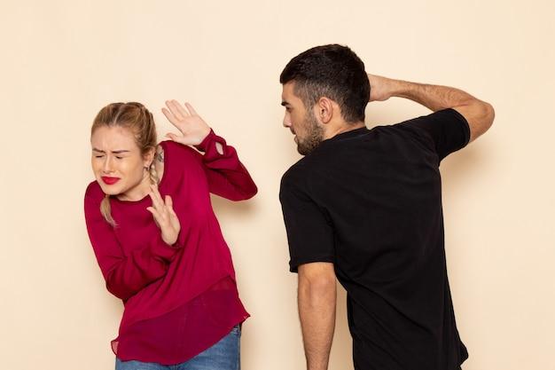 Widok z przodu młoda kobieta w czerwonej koszuli cierpi z powodu fizycznych zagrożeń i przemocy na kremowym obszarze kobieta tkaniny przemoc fotograficzna w domu