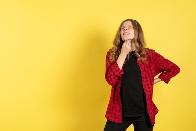 Widok z przodu młoda kobieta w czerwonej koszuli w kratkę pozowanie na żółtym tle model dziewczyny kobieta emocja ludzka kobieta