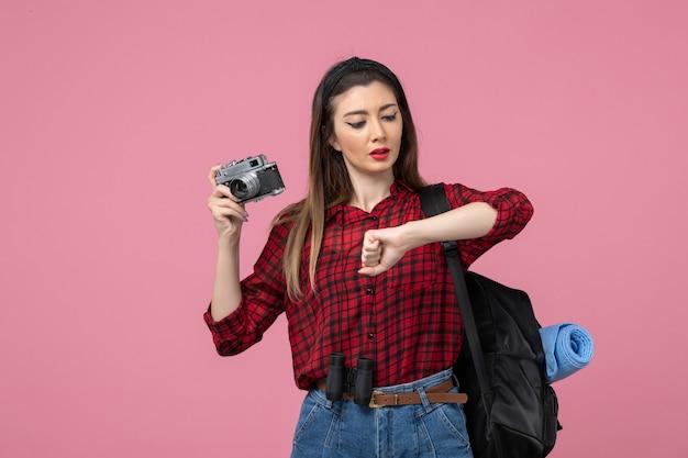 Widok z przodu młoda kobieta w czerwonej koszuli z aparatem na różowym piętrze zdjęcie modelu kobieta