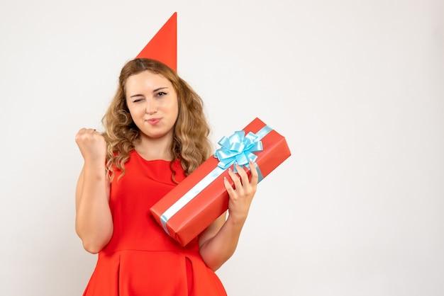 Widok z przodu młoda kobieta w czerwonej sukience świętuje boże narodzenie z prezentem