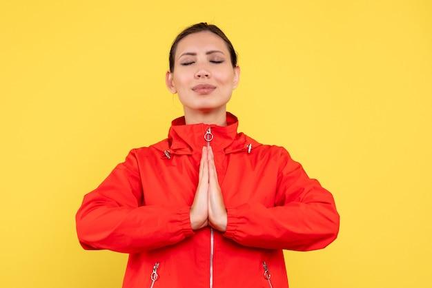 Widok z przodu młoda kobieta w czerwonym płaszczu modląc się na żółtym tle
