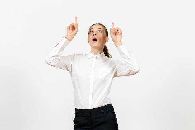 Widok z przodu młoda kobieta w eleganckiej białej bluzce wskazująca na sufit na białym tle kobieta praca w biurze pani pracownica
