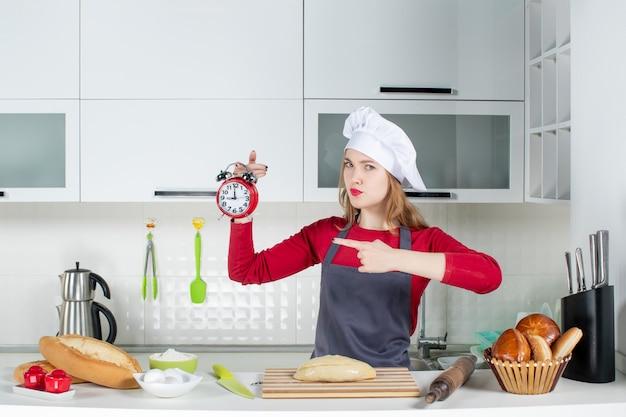 Widok z przodu młoda kobieta w kapeluszu kucharza trzymająca czerwony budzik
