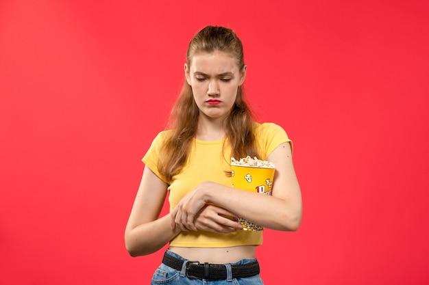Widok z przodu młoda kobieta w kinie trzymając pakiet popcornu i podkreślił na czerwoną ścianę filmy teatr kino przekąskę zabawny film