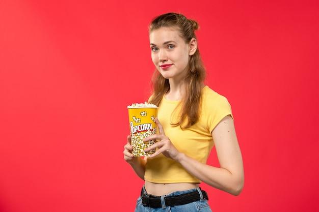 Widok z przodu młoda kobieta w kinie trzymając pakiet popcornu i uśmiechając się na czerwonej ścianie filmy teatralne kino kobiece film zabawa