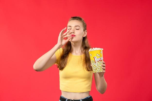 Widok z przodu młoda kobieta w kinie trzymając pakiet popcornu na jasnoczerwonych filmach ściennych kino teatralne