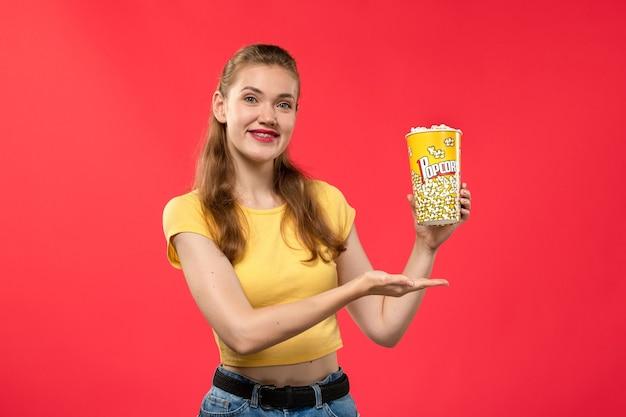 Widok z przodu młoda kobieta w kinie trzymając pakiet popcornu z lekkim uśmiechem na czerwonej ścianie filmy teatralne kino kobiece film zabawa