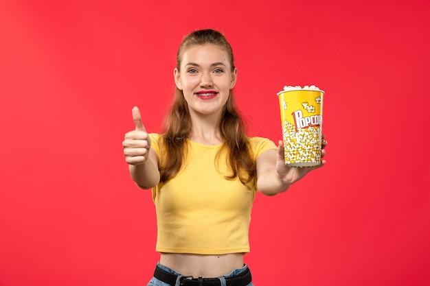 Widok z przodu młoda kobieta w kinie trzymając pakiet popcornu z uśmiechem na jasnoczerwonej ścianie kina kino zabawa film