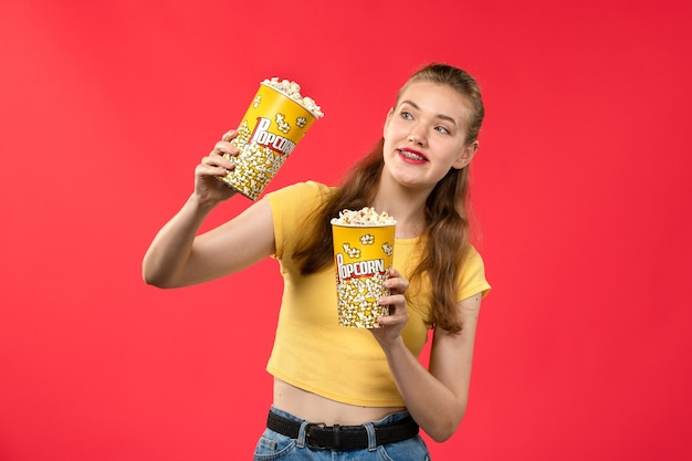 Widok z przodu młoda kobieta w kinie trzymając pakiety popcornu na jasnoczerwonej ścianie kino kino kobiece film zabawa