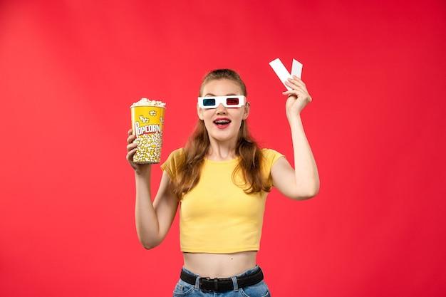 Widok z przodu młoda kobieta w kinie trzymając popcorn i bilety na czerwonej ścianie kino kino kobiet kolory